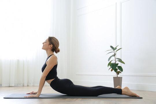 Young woman practicing high cobra asana in yoga studio. Bhujangasana pose