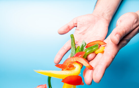 Closeup of the hands throwing away the fresh colored peppers on a blue background