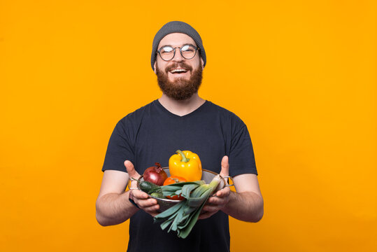 Charming young hipster man with beard holding raw vegetables over yellow background.
