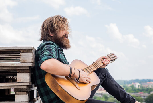 time to relax. bearded man in checkered shirt sing song. music performer musician. musical string instrument. mature charismatic male guitarist. guy with beard and moustache play guitar