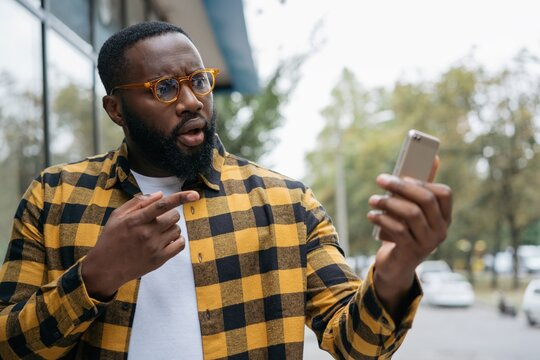 Emotional African American man shopping online, pointing finger on mobile phone screen. Influencer using smartphone, streaming video, communication with subscribers
