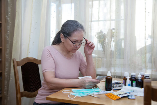Portrait of  mature woman with  pile of medicines on  table