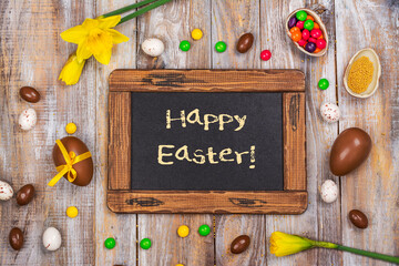 Easter background with yellow daffodils, chocolate eggs and candies. Copy space