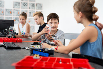 School children programs a robot in the classroom