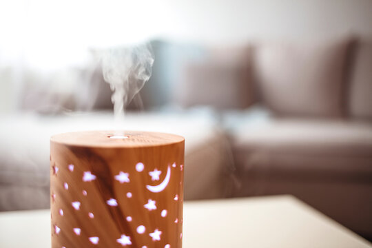 Essential oils diffusing at home in the morning light. Essential Oil Diffuser. Small air humidifier at home.  Aroma health essence, welness aromatherapy home spa fragrance tranquil theraphy