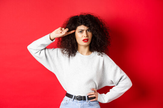 Are you stupid. Annoyed and confused girl with curly hair, pointing at head and scolding person being crazy or strange, standing on red background