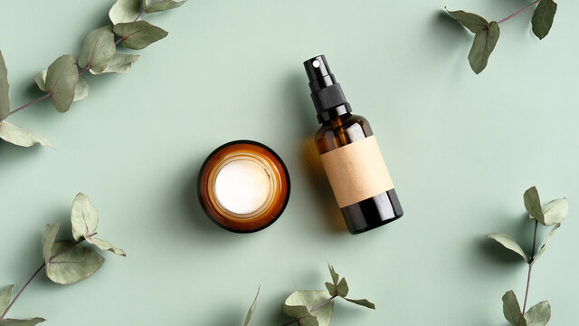 SPA cosmetics products branding mockup. Jar of moisturizer cream and amber glass spray bottle on green background with eucalyptus leaves. Organic herbal beauty products