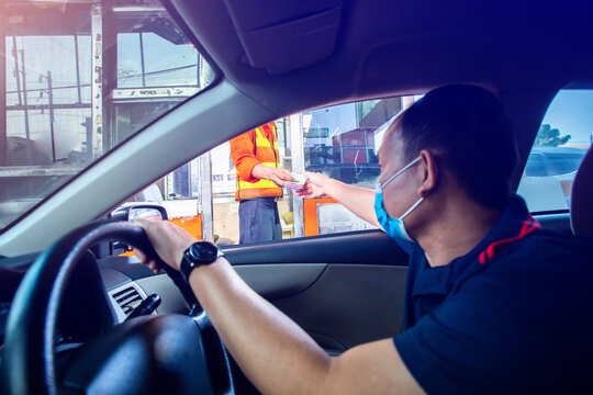 Selective focus to cashier staff with blurry driver pay toll to the expressway.