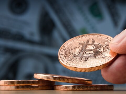 Female hand showing bitcoin coin.Dollar banknotes as a background.Virtual cryptocurrency concept.Bitcoins trading.selective focus.close-up