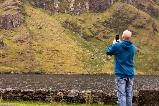 Bald male tourist taking picture of mountains on his smart phone. Travel concept. Connemara, Ireland.