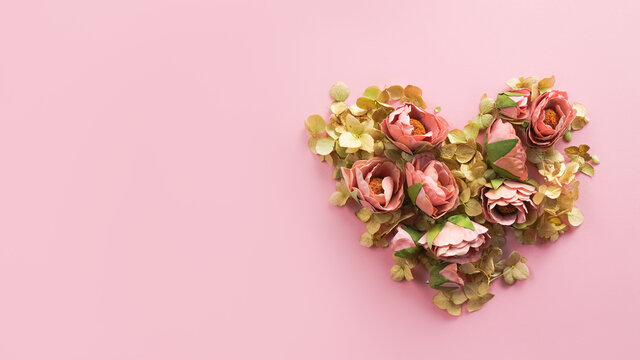 Heart made of flowers on pink background. Copy space, 16x9 romantic banner. Love, spring, Valentines day, wedding concept.