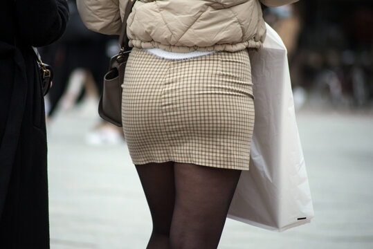 Closeup of girl walking in the street with a beige mini skirt