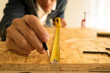 Obraz Close-up Of Carpenter Measuring Wood In Carpentry Workshop - fototapety do salonu