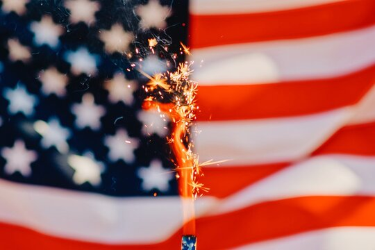Close-up Of Lit Sparkler Against American Flag