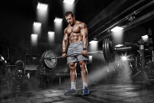 Athlete muscular brutal bodybuilder training workout with heavy barbell in the gym