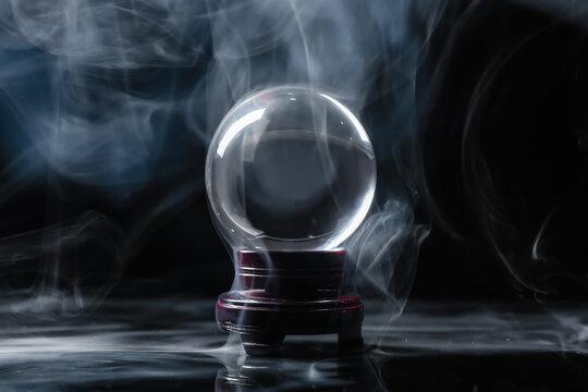 Crystal ball of fortune teller in smoke on dark background