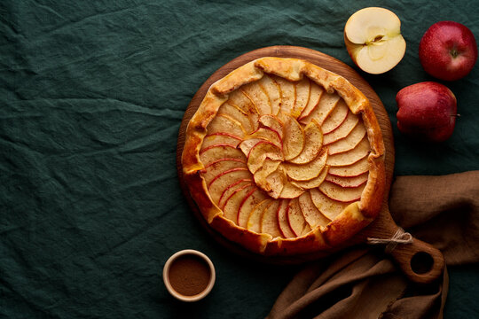 Apple pie, galette with fruits, sweet pastries on dark green tablecloth, sweet crostata on cutting wooden board, side view, autumn or winter food, copy space