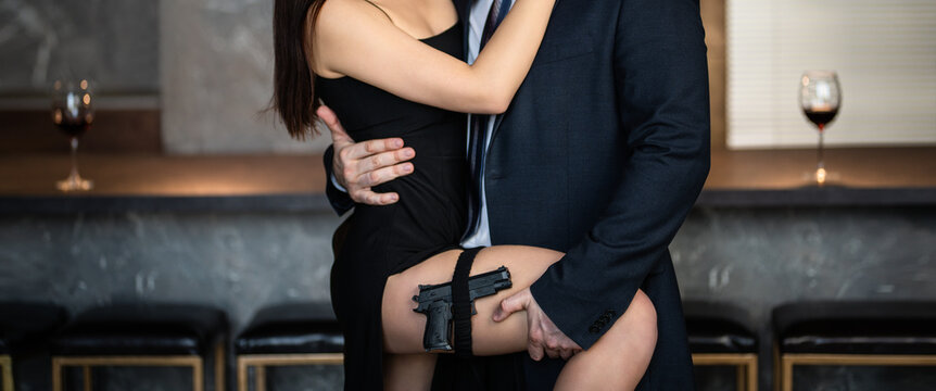 A man in a suit and a women with a gun in a black dress with a slit, loft. Elegant couple in love. Valentine's Day. Banner.