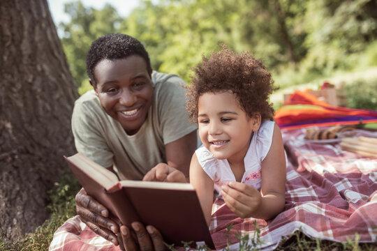 African american man and his kid reading a book together