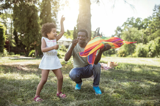 Dark-skinned man showing to his kid how to play with the kite