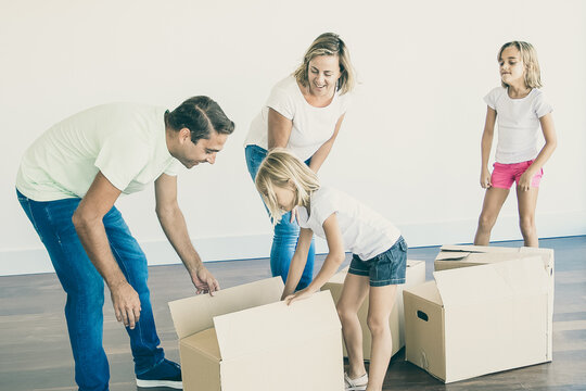 Smiling couple with two daughters unpacking boxes in empty room. Blonde mother and middle-aged father with their children standing near carton boxes. Mortgage, relocation and moving day concept
