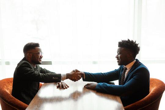 two handsome african men in suits shaking hands indoors