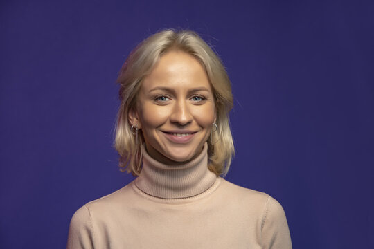 Studio portrait of a smiling blonde woman 25-30 years old on a color background, close-up, selective focus.