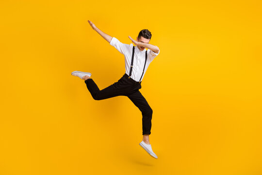 Full length body size photo of jumping man dancing hip-hop showing hype dab sign isolated on bright yellow color background