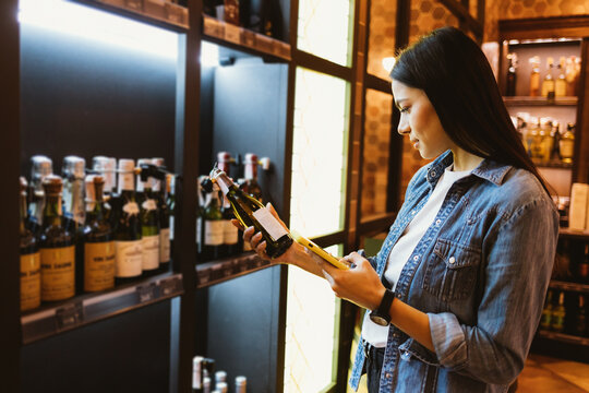 Beautiful young brunette woman buying wine examines label holding bottle