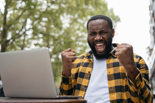 Emotional African American man win online lottery celebration success. Good news, promote at work,  successful deal concept