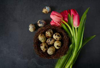 pink tulips and Easter eggs on stone surface