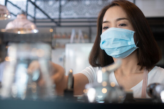 Asian barista women wearing face masks to prevent contagious diseases and serve customers in the coffee shop. The concept of prevention from COVID 19