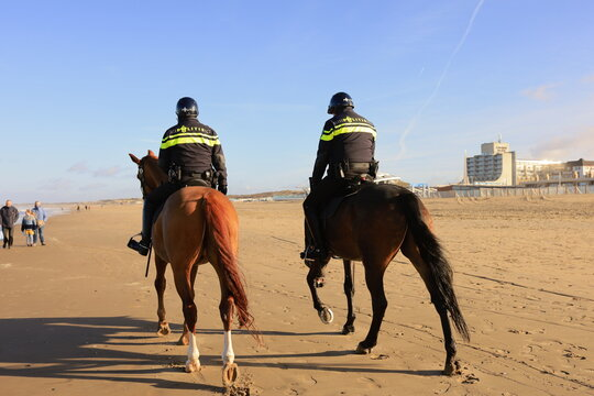 Scheveningen, The Hague, The Netherlands, 22 January 2021: two policemen riding a horse on a beach in Scheveningen, The Hague, The Netherlands