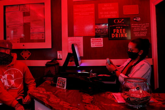 An employee wearing a protective face mask counts money at the entrance to the Oz Ladies' and Gentlemen's Nightclub ahead of the Tampa Bay area weekend NFL' Super Bowl LV amid the ongoing spread of the coronavirus disease (COVID-19) at in Clearwater