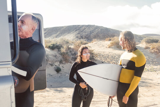 Three friends going to surf in the sea
