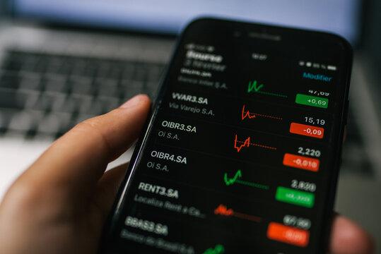 Pessoa usando o aplicativo da bolsa de valores no iphone (Bovespa, Brasil)