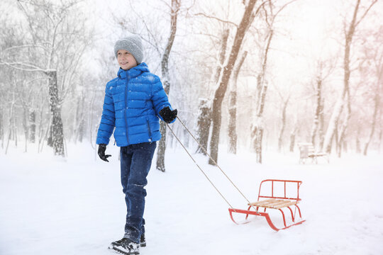 Cute little boy with sleigh outdoors on winter day