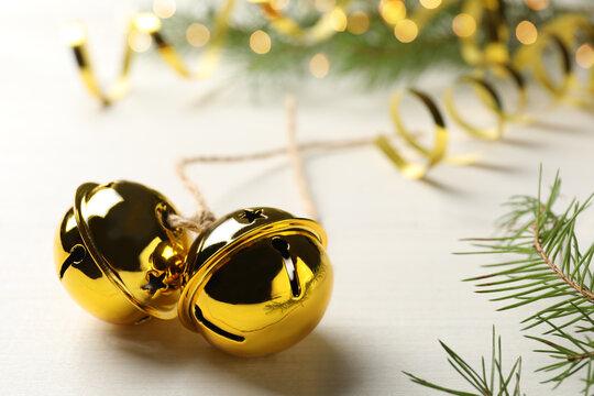 Golden sleigh bells and fir branch on white table, closeup