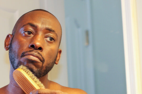 A portrait of an African-American man brushing his beard while looking in a bathroom mirror