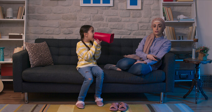 The mother wearing the headscarf sits on the sofa and watches TV. Little girl yelling with a red bullhorn to her mother, who is a TV addict.