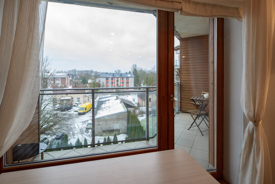 Modern interior of luxury apartment. Window and glass door to balcony. View of city.