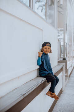 Funny preschool boy in stylish clothing with cap sits near white wall on seaside and shows shaka symbol.