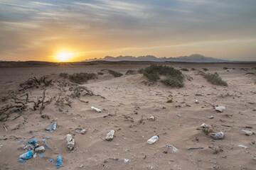 Fototapeta Piękny krajobraz o zachodzie słońca zanieczyszczony śmieciami, plastikiem i odpadkami obraz