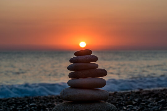Stack Of Stones At Beach During Sunset