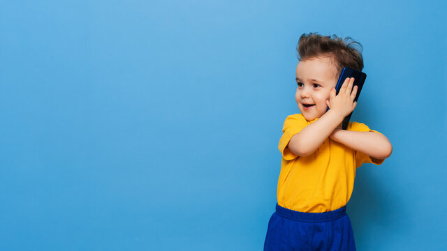 A little boy is talking on a mobile phone. Studio photo on a blue background. Space for text