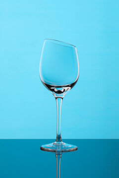 Glass wine goblet with beveled top edge on blue background