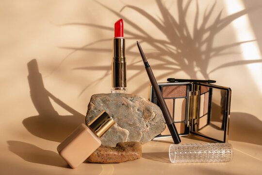 Makeup cosmetics in beige tones. Red lipstick, eye shadow, eyebrow pencil, foundation. The shadow of a plant on a beige background. Trendy cosmetics .