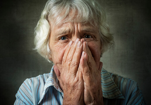 Portrait Of Senior Woman Covering Face Against Wall