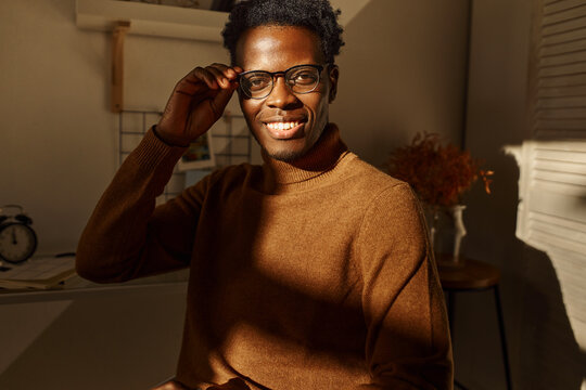 Ethnicity, race and diversity concept. Indoor portrait of happy successful young black expressing positive emotions, seated at desk in stylish apartment, adjusting his eyeglasses, smiling
