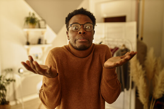 Indoor shot of puzzled funny young Afro American man shrugging shoulders in bewilderment spreading hands, staring at camera with uncertain confused facial expression, making decision or choice.